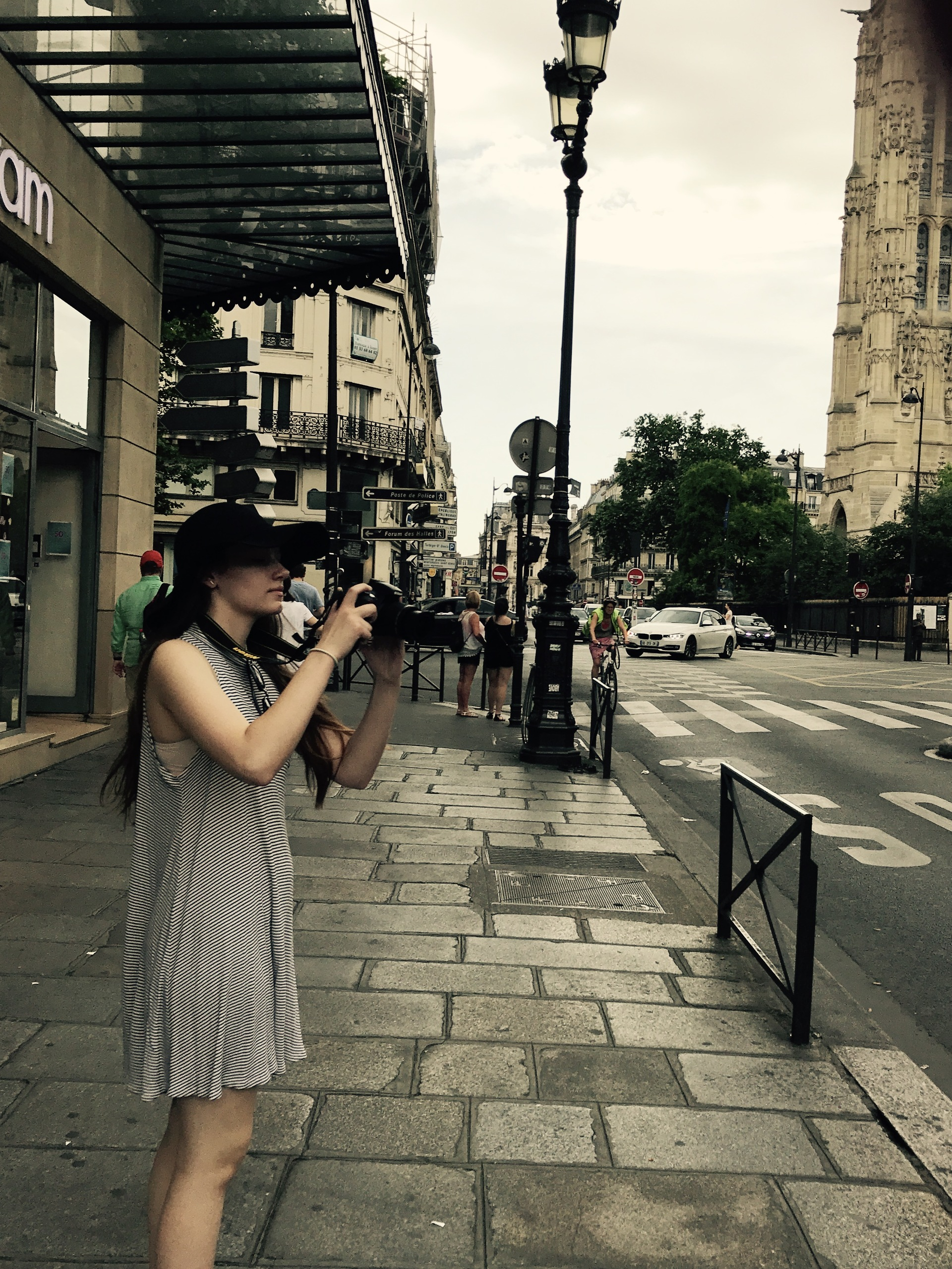 Young woman capturing photo from sidewalk