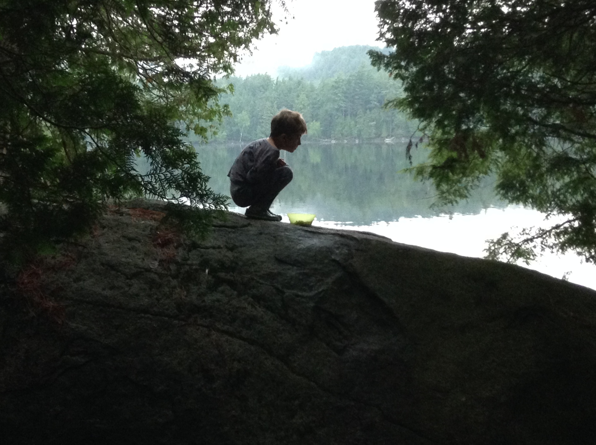 Squirrel boy. Breakfast in pajamas on the rock during a family cannot trip
