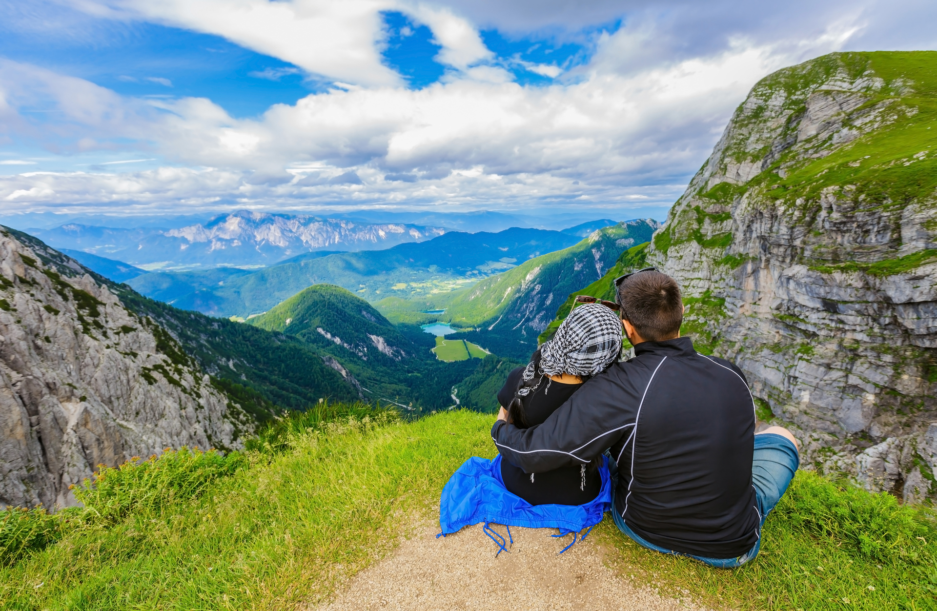Couple sitting on top of mountain overlooking the view