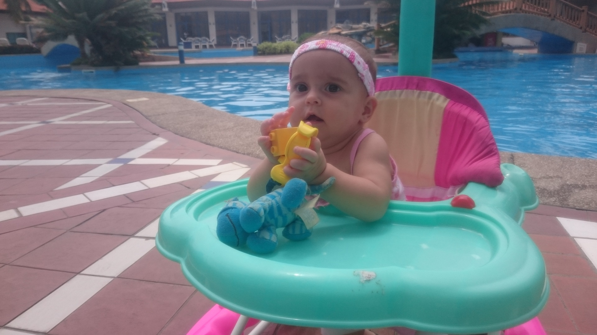 Foap cute toddler at poolside baby girl in walking chair by