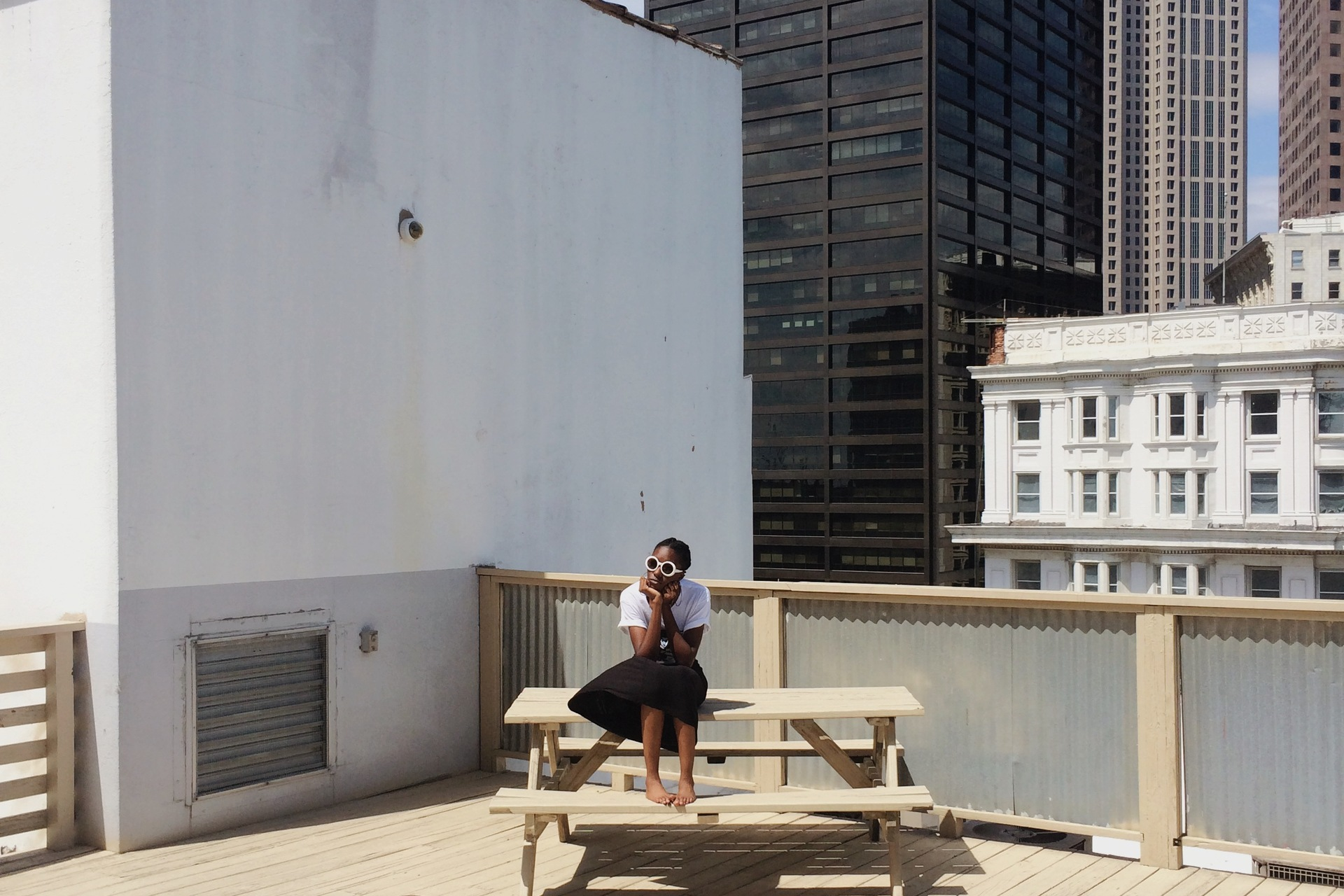 African woman sitting on wooden bench at terrace